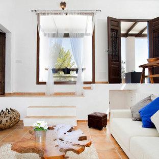 Mittelgroßes, Offenes Mediterranes Wohnzimmer ohne Kamin mit weißer Wandfarbe, Terrakottaboden und Wand-TV in Barcelona