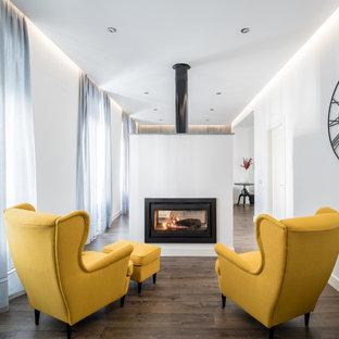 Diseño de sala de estar con biblioteca abierta, contemporánea, de tamaño medio, sin televisor, con paredes blancas, suelo de madera oscura, chimenea de doble cara y marco de chimenea de metal
