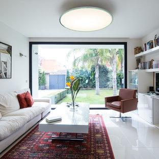 Modelo de sala de estar con biblioteca cerrada, actual, de tamaño medio, sin chimenea, con paredes blancas y televisor independiente