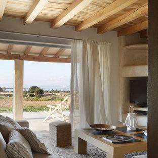 Imagen de sala de estar abierta, rústica, de tamaño medio, con paredes blancas, moqueta y televisor independiente