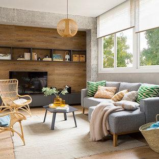 Imagen de sala de estar actual, sin chimenea, con paredes grises, suelo de madera clara, televisor independiente y suelo beige