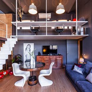 Imagen de sala de estar abierta, contemporánea, con paredes azules, suelo de madera en tonos medios, televisor independiente y suelo marrón