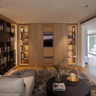 Foto de sala de estar con biblioteca cerrada, actual, sin chimenea, con paredes blancas, suelo de madera en tonos medios, televisor retractable y suelo marrón