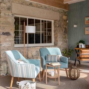 ビルバオの中サイズの北欧スタイルのおしゃれなオープンリビング (ライブラリー、青い壁、ラミネートの床、暖炉なし、テレビなし、茶色い床) の写真