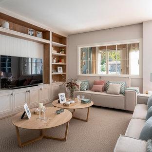 Modelo de sala de estar abierta, escandinava, grande, sin chimenea, con paredes beige, suelo laminado, televisor independiente y suelo beige