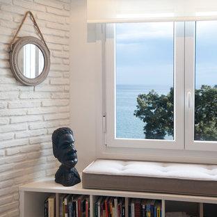ビルバオの中サイズのビーチスタイルのおしゃれなファミリールーム (ライブラリー、白い壁、ラミネートの床、壁掛け型テレビ) の写真