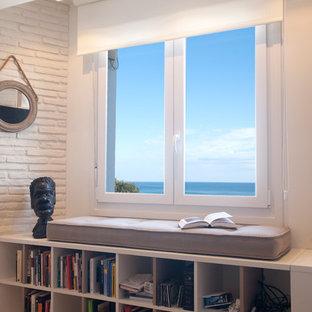 ビルバオの中サイズのビーチスタイルのおしゃれなファミリールーム (ライブラリー、白い壁、ラミネートの床、壁掛け型テレビ、茶色い床) の写真