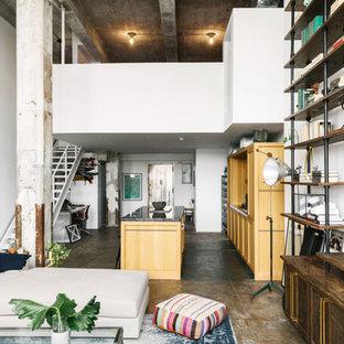 Ejemplo de sala de estar con biblioteca abierta, industrial, grande, con paredes blancas, suelo de cemento y televisor colgado en la pared