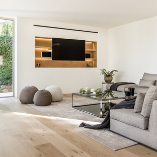 Diseño de sala de estar abierta, actual, con paredes blancas, suelo de madera clara, chimeneas suspendidas, pared multimedia y marco de chimenea de metal