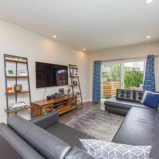 Ispirazione per un soggiorno minimalista di medie dimensioni e stile loft con libreria, pareti beige, pavimento in compensato, nessun camino, parete attrezzata e pavimento marrone