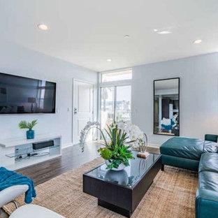 Idee per un grande soggiorno minimal stile loft con libreria, pareti bianche, pavimento in compensato, nessun camino, TV a parete e pavimento marrone