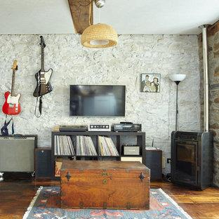 Idées déco pour une salle de séjour campagne avec une salle de musique, un mur beige, un sol en bois brun, un poêle à bois et un téléviseur fixé au mur.