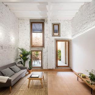 Modelo de sala de estar abierta, actual, de tamaño medio, con paredes blancas, suelo de baldosas de terracota y suelo rojo