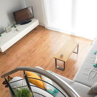 Modelo de sala de estar abierta, escandinava, pequeña, con paredes blancas, suelo laminado, televisor en una esquina y suelo marrón