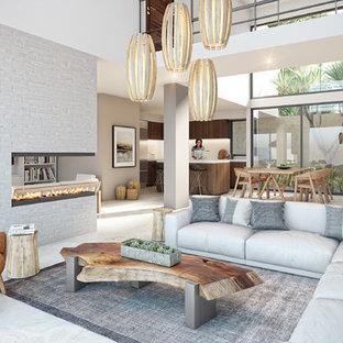 他の地域の大きいコンテンポラリースタイルのおしゃれなファミリールーム (グレーの壁、磁器タイルの床、両方向型暖炉、レンガの暖炉まわり、ベージュの床) の写真
