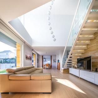 Diseño de sala de estar abierta, actual, extra grande, con suelo de madera clara y televisor independiente