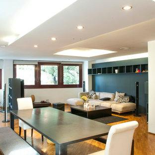 Aménagement d'une grande salle de séjour mansardée ou avec mezzanine moderne avec un mur noir, un sol en bois brun, un téléviseur indépendant et un sol jaune.