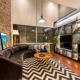 Imagen de sala de estar industrial con paredes multicolor, suelo de madera en tonos medios y televisor colgado en la pared