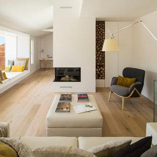 バルセロナの中サイズの北欧スタイルのおしゃれなファミリールーム (白い壁、無垢フローリング、テレビなし、コーナー設置型暖炉) の写真