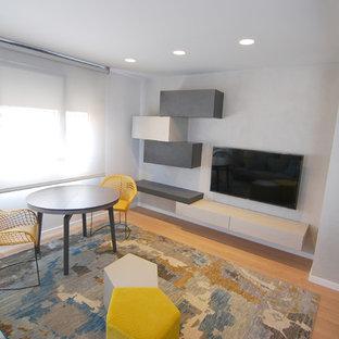 Foto de sala de estar abierta, minimalista, pequeña, sin chimenea, con paredes grises, suelo de baldosas de porcelana y televisor colgado en la pared