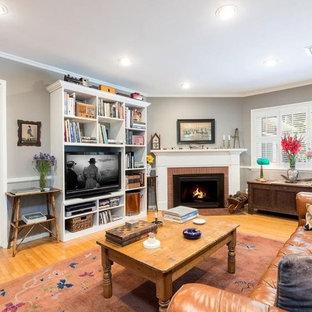 Imagen de sala de estar con biblioteca abierta, campestre, grande, con paredes grises, suelo de madera en tonos medios, estufa de leña, marco de chimenea de ladrillo, pared multimedia y suelo marrón