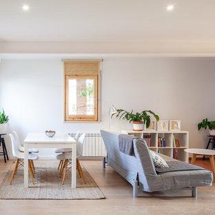 Imagen de sala de estar abierta, actual, pequeña, sin televisor, con paredes blancas, suelo de madera clara, estufa de leña y suelo beige