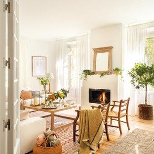 Modelo de sala de estar cerrada, tradicional renovada, de tamaño medio, sin televisor, con paredes blancas, suelo de madera en tonos medios y chimenea tradicional