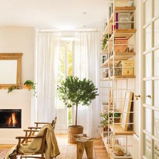 Diseño de sala de estar con biblioteca abierta, romántica, de tamaño medio, con paredes blancas y suelo de madera en tonos medios