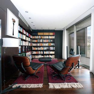 Foto de sala de estar con biblioteca actual, grande, con suelo de madera oscura, paredes negras y suelo marrón