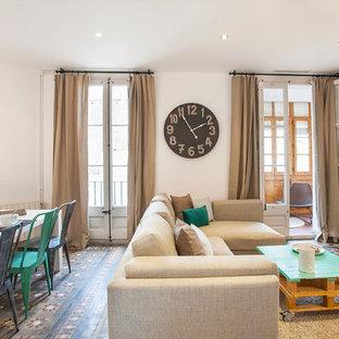 Modelo de sala de estar abierta, mediterránea, grande, sin chimenea y televisor, con paredes blancas y suelo de baldosas de cerámica
