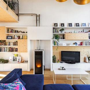 Modelo de sala de estar con biblioteca abierta, contemporánea, grande, con paredes blancas, suelo de madera clara, estufa de leña, marco de chimenea de metal, televisor independiente y suelo beige