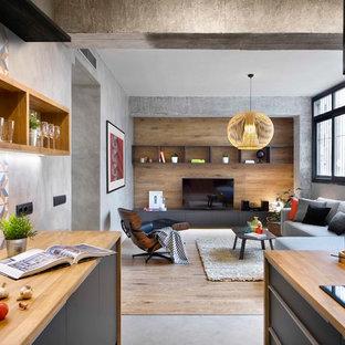 Inredning av ett industriellt mellanstort allrum med öppen planlösning, med betonggolv, grått golv och en fristående TV