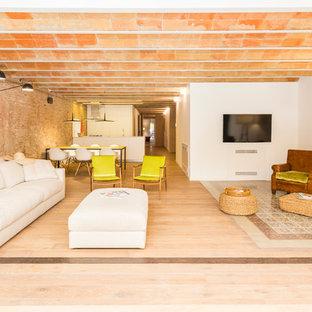 Ejemplo de sala de estar abierta, mediterránea, grande, con paredes blancas, suelo de madera clara, televisor colgado en la pared y suelo violeta
