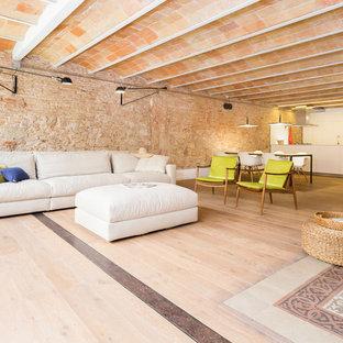 Imagen de sala de estar abierta, mediterránea, grande, con paredes blancas, suelo de madera clara, televisor colgado en la pared y suelo violeta