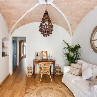 Modelo de sala de estar cerrada, mediterránea, de tamaño medio, con paredes blancas, suelo de madera en tonos medios y suelo marrón