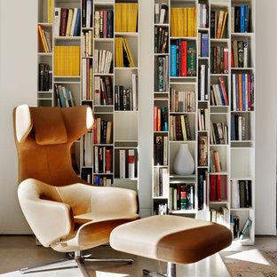 Foto de sala de estar con biblioteca abierta, actual, pequeña, sin chimenea y televisor, con paredes blancas y suelo de piedra caliza