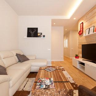 Ejemplo de sala de estar abierta, contemporánea, de tamaño medio, con paredes grises, suelo de madera clara, televisor independiente y suelo beige