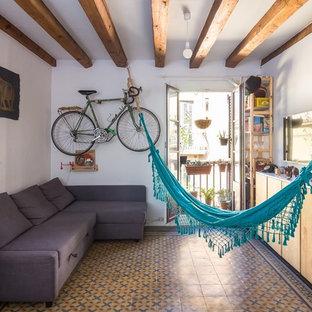 Diseño de sala de estar abierta, marinera, pequeña, con paredes blancas, suelo de baldosas de cerámica, televisor colgado en la pared y suelo multicolor