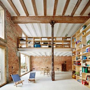 Immagine di un grande soggiorno industriale con libreria, pareti arancioni, pavimento in cemento, nessun camino e nessuna TV