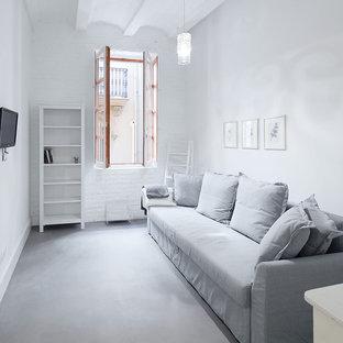 Imagen de sala de estar mediterránea con televisor colgado en la pared, paredes blancas, suelo de cemento y suelo gris