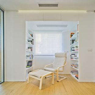 Ejemplo de sala de estar con biblioteca abierta, contemporánea, pequeña, sin chimenea y televisor, con paredes blancas y suelo de madera en tonos medios
