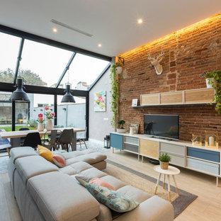 Diseño de sala de estar abierta, industrial, grande, sin chimenea, con paredes grises, suelo de madera clara y televisor independiente