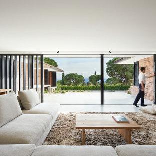 Diseño de sala de estar con biblioteca abierta, minimalista, grande, sin chimenea, con paredes beige, suelo de cemento, televisor retractable y suelo gris