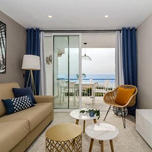 Foto de sala de estar cerrada, marinera, con paredes beige, televisor independiente y suelo beige