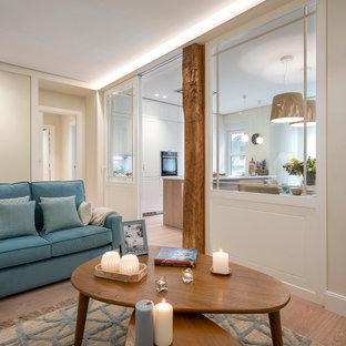 Esempio di un soggiorno tradizionale di medie dimensioni e aperto con libreria, pareti beige, pavimento in laminato, nessun camino, TV a parete e pavimento marrone