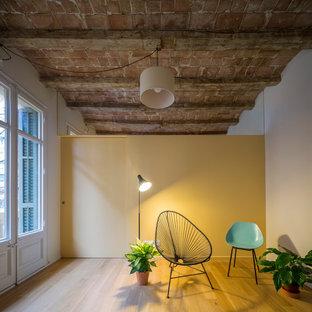 Imagen de sala de estar urbana, pequeña, sin chimenea y televisor, con paredes amarillas y suelo de madera en tonos medios