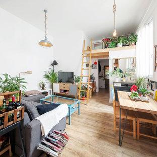 Imagen de sala de estar abierta, actual, de tamaño medio, con paredes blancas, suelo beige, suelo de madera clara y televisor independiente