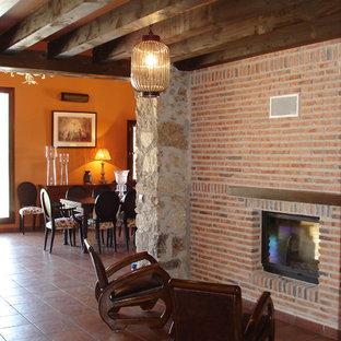 マドリードの大きいカントリー風おしゃれなファミリールーム (テラコッタタイルの床、薪ストーブ、レンガの暖炉まわり) の写真