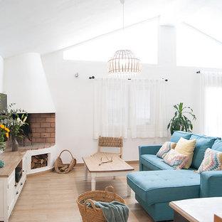 Ejemplo de sala de estar abierta, mediterránea, con suelo de baldosas de porcelana, chimenea de esquina, marco de chimenea de yeso, televisor colgado en la pared, suelo beige y paredes blancas