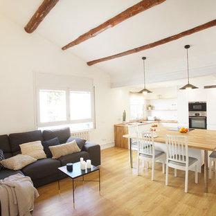 Imagen de sala de estar abierta, mediterránea, de tamaño medio, con suelo de madera clara, paredes blancas y suelo beige